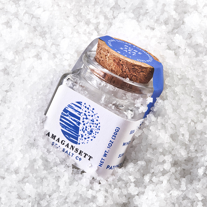 Glass jar of natural, solar evaporated finishg salt on a bed of Amagansett Sea Salt